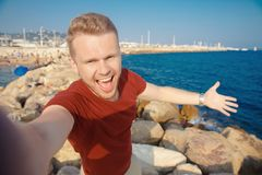 Male traveler happy makes selfie photo on background of beach and sea. Travel concept royalty free stock photography