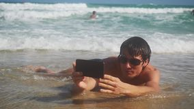 Male traveler holding smart phone in hands taking selfie lying on the beach on seashore Tourist on summer vacation. Male traveler holding smart phone in hands stock video footage