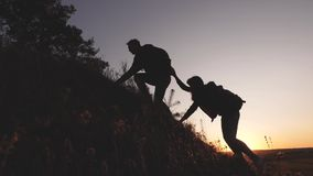 Male traveler holds out his hand to female traveler climbing a hilltop. Tourists climb the mountain in the sunset. Male traveler holds out his hand to female stock video