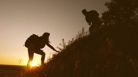 Male traveler holds out his hand to a female traveler climbing hilltop. Tourists climb mountain in sunset, holding hands. Male traveler holds out his hand to stock video