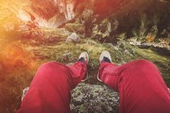Male traveler legs of a traveler sitting on a rock against a cliff, point of view shot. Travel Lifestyle Adventure Vacations stock images