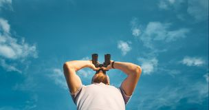 Male Traveler Looking Through Binoculars In The Distance Against The Sky. Low Angle Point Shoot royalty free stock photography