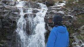 Male traveler looks at the waterfall. Close-up. He rests in the mountains and admires the beautiful view. The unity of. Male traveler looks at the waterfall. He stock video footage