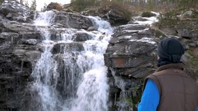 Male traveler looks at the waterfall. Close-up. He rests in the mountains and admires the beautiful view. Male traveler looks at the waterfall. He rests in the stock video footage