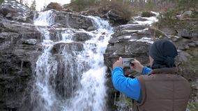 Male traveler looks at the waterfall. Close-up. He rests in the mountains and admires the beautiful view. He is. Male traveler looks at the waterfall. He rests stock video footage