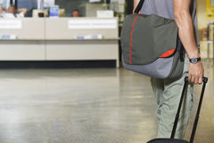Male Traveler With Luggage In Lobby. Closeup side view midsection of a male traveler with bags at the airport Stock Photography