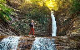 Male traveler makes self-portrait against backdrop of landmark waterfall Gelendzhik, North Caucasus, Russia. The tourist makes a self-portrait against the Stock Photography