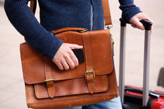 Male traveler with mobile phone and luggage. Close up portrait of man with mobile phone, leather shoulder bag and suitcase standing outdoors Royalty Free Stock Photo