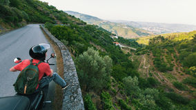 Male traveler on a motorcycle looking from the height of the serpentine road of the green valley. Portugal. Male traveler on a motorcycle looking from the Royalty Free Stock Photo