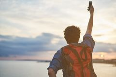 Male traveler photographing himself at the seaside. Cheerful young man is making selfie on cellphone while standing near the sea. Focus on backpack on his back Royalty Free Stock Image