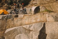 Male traveler in protective helmet standing with mountain bike and pointing by finger to friend near tent on rocky. Cliff royalty free stock images
