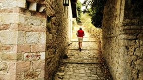 Male traveler in red tshirt walks in ancient Mediterranean fortress on vacation royalty free stock photography