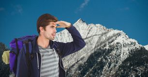 Male traveler shielding eyes while carrying backpack on mountain. Digital composite of Male traveler shielding eyes while carrying backpack on mountain Stock Photography
