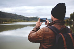 Male traveler shoots video on cell telephone of mountains and lake during journey Royalty Free Stock Photo