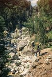 Hiker in the wild nature on the trail to Tahtali mount. Male traveler shot from above exploring rocks and rivulet on a sunny day in Turkey Royalty Free Stock Photo