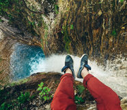 Male Traveler sitting on cliff with waterfall view. Travel Lifestyle adventure vacations concept. Couple male feet on a rock on a waterfall background Stock Photo