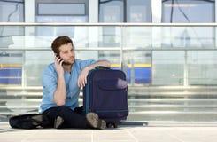Male traveler sitting on floor talking on mobile phone Stock Images