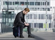 Male traveler sitting on suitcase reading text message Stock Photo