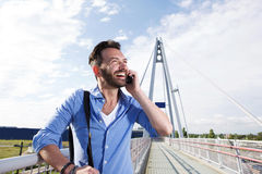 Male traveler standing on bridge and talking on cell phone. Portrait of happy male traveler standing on bridge and talking on cell phone Stock Image