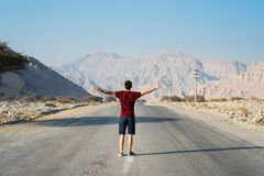 Man standing on the empty dessert road. Male traveler standing on the empty dessert road royalty free stock photo