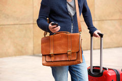 Male traveler standing outdoors with cellphone and bags. Close up portrait of male traveler standing outdoors with cellphone and travel bag Stock Photos