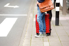 Male traveler standing by the street with suitcase. Side view portrait of male traveler standing by the street with suitcase Royalty Free Stock Photography