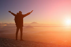 Male traveler is standing on top of a mountain. With a backpack and put his hands up Stock Photos