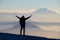 Male traveler is standing on top of a mountain. With a backpack and put his hands up Royalty Free Stock Photo