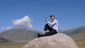 Male traveler surfing phone and resting on stone in nature. Tian Shan mountains, Kyrgyzstan. Man using smartphone outdoor stock footage