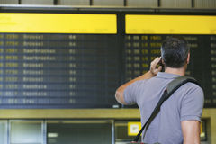 Male Traveler Using Cellphone By Flight Status Board. Rear view of a male traveler using mobile phone in front of flight status board in airport Stock Images