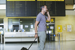 Male Traveler Using Cellphone By Flight Status Board. Side view of a male traveler using mobile phone in front of flight status board in airport Stock Image