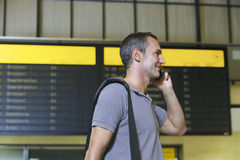 Male Traveler Using Cellphone By Flight Status Board. Side view of a male traveler using mobile phone in front of flight status board in airport Stock Photo