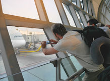Male traveler using mobile phone to take photo of an airplane parking at jet bridge, waiting for passenger to board at airport. Stock Photos