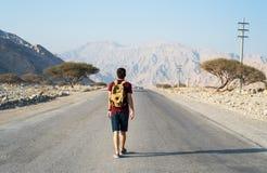 Man walking on the empty dessert road. Male traveler walking on the empty dessert road stock photography