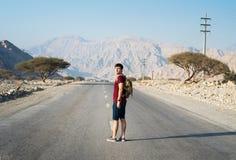 Man walking on the empty dessert road. Male traveler walking on the empty dessert road stock photo