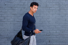 Male traveler walking with mobile phone and bag Royalty Free Stock Photos