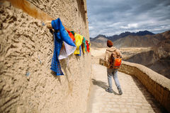 Male traveler walking in the monastery with colorful prayer flags in Leh, Ladakh, India.  Stock Photography
