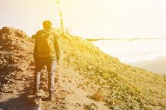 Male traveler walking uphill on sand dune leading to monastery in Leh, Ladakh, India. Light Leak Orange tone Stock Photos