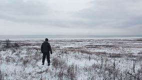Male traveler walking in the winter steppe. People and wildlife stock footage