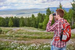 Male traveler watching binoculars into the distance against a forest and a cloudy sky stock image