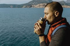Male traveler wearing a sports vest stands on a mountain with a. Backpack and drinks from thermos against the sea background in Montenegro Stock Image