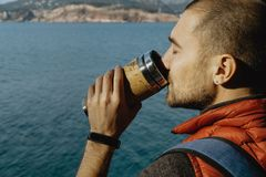 Male traveler wearing a sports vest stands on a mountain with a. Backpack and drinks from thermos against the sea background in Montenegro Stock Photography