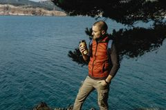Male traveler wearing a sports vest stands on a mountain with a. Backpack and thermos in the sea background in Montenegro Royalty Free Stock Images