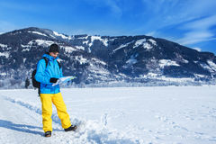 Male traveler in winter clothing. Hiking with a map Stock Photo
