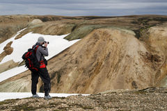 Male traveller. Young male traveller, photographer taking photos of the beautiful view of mountains in Landmannalaugar region ofIceland Royalty Free Stock Photo