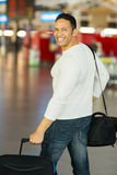 Male traveller airport. Mid age male traveller walking in airport with luggage Royalty Free Stock Images