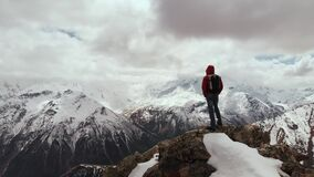A male traveller with a backpack stands on top of a cliff against the backdrop of snow-capped mountain peaks and low