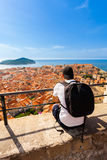 Male traveller looking at the panorama of Dubrovnik and sea. Male traveller looking at the panorama of the old city of Dubrovnik from the fort. Travel to Stock Images