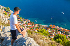Male traveller looking at the panorama of Dubrovnik and sea. Male traveller looking at the panorama of the old city of Dubrovnik from the mountain. Travel to Stock Image