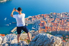 Male traveller make a photo of Dubrovnik to the phone. Male traveller make a panoramic photo of the old city of Dubrovnik from the mountain to his phone for Royalty Free Stock Images